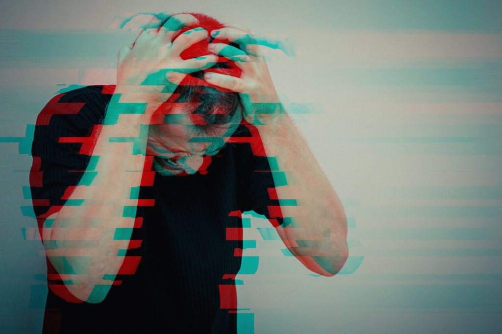 Portrait of a one sad man standing outdoors near the house at the day time. Concept of sadness. Glitched style photo.